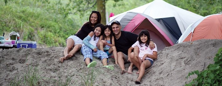 Family sitting on sand dune with tent behind them at Long Point Provincial Park