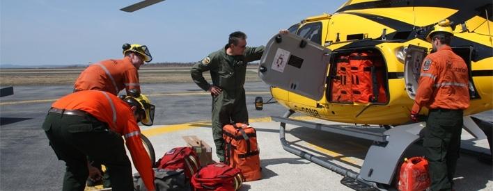 An Ontario FireRanger crew loads gear into a Eurocopter EC-130 B4 aircraft in preparation for a wildfire dispatch.