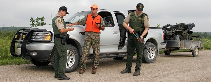 Conservation officers checking a hunter