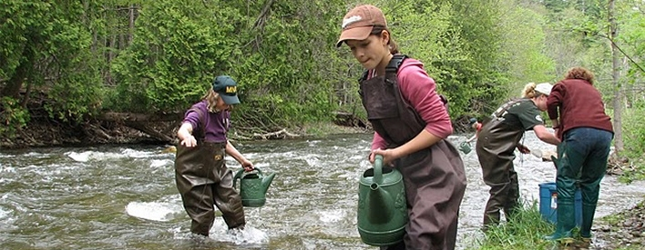 Youths stocking fish in Southern Ontario