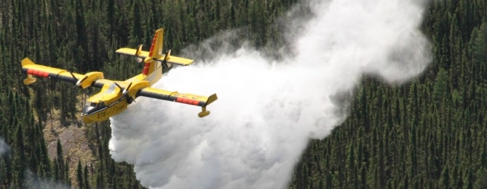 A CL-415 heavy waterbomber fights forest fires from the air in Ontario, dropping water to stop the advance of fire while FireRanger crews attack from the ground.