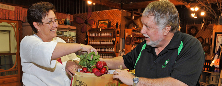 Ted McMeekin, Minister of Agriculture, Food and Rural Affairs is assisted by Heather Harding while shopping for local produce at the Lindley Farm and Market in Ancaster. Minister McMeekin toured the farm and market to celebrate the start of Agriculture Week (October 1 to 7, 2012).
