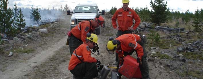 Ontario FireRangers refueling fire torches in order to burn off land before the main fire gets there.