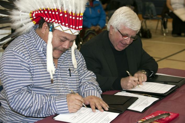 Le Grand chef (Ogichidaa) Warren et M. Rick Bartolucci, ministre du Développement du Nord et des Mines, signent une lettre d'engagement entre le Grand conseil du Traité no 3 et la province pour réaffirmer l'engagement mutuel des deux parties à travailler ensemble à créer des possibilités de développement économique pour les collectivités membres du Traité no 3. (M. Michael Gravelle, ministre des Richesses naturelles, n'a pu assister à la cérémonie.)