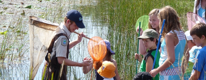 An Ontario Parks staff member helps children investigate amarsh at Presqu'ile Provincial Park. (Ministry of NaturalResources, David Bree, 2008)