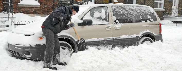 Man shovelling deep snow around his minivan