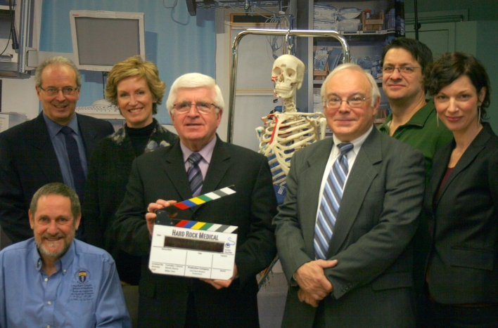 Rick Bartolucci, Minister of Northern Development and Mines and Chair of the Northern Ontario Heritage Fund Corporation, announced an investment of $1 million from the Province in a new TV series called Hard Rock Medical to be set and produced in Northern Ontario. The minister (holding clapperboard) was joined by (left to right, standing): Mark Palumbo, President of the Board of Directors, Music and Film in Motion; Lisa de Wilde, Chief Executive Officer, TVO; Frank Taylor, Executive Producer; Derek Diorio, Co-creator/Producer/Director/Writer; Tracy Legault, Co-producer, all with Hard Rock Medical; and (seated) Dr. Roger Strasser, Dean of the Northern Ontario School of Medicine.