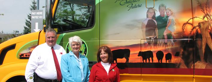 Jim Clark (directeur général, Ontario Cattle Feeders' Association [OCFA]), Liz Sandals (députée de la circonscription provinciale de Guelph) et Leona Dombrowsky (ministre de l'Agriculture, de l'Alimentation et des Affaires rurales), près de la cabine du camion qui tire la remorque de 72 pieds, oú se trouve la cuisine éducative There's No Taste Like Home, dont le but est de faire connaître les produits agricoles et les agriculteurs de l'Ontario.