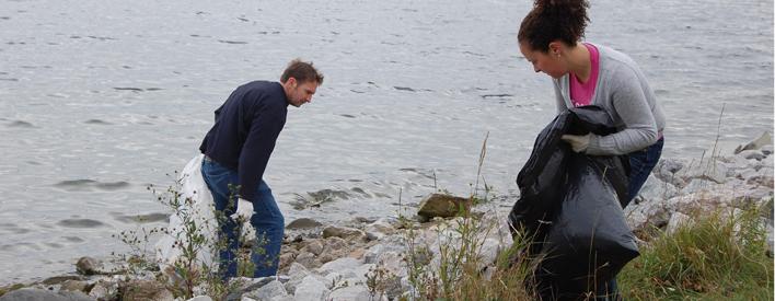 Glenn Holland et Kam Naisbitt ramassent des débris sur les rochers le long du rivage.