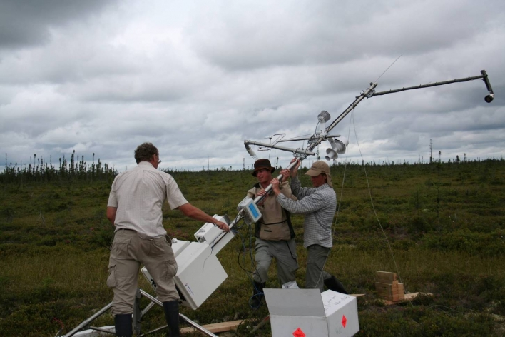 Crew hoisting the assembled Kinoje Lake Carbon Flux monitoring station into place.
