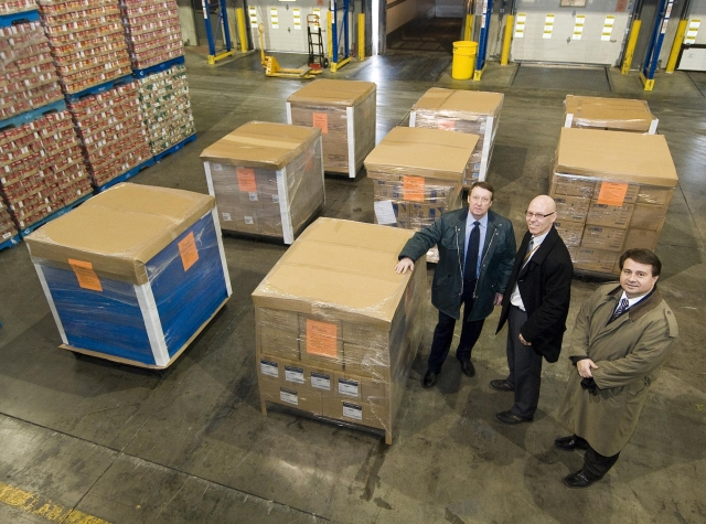Ontario government officials stand next to the eight pallets of emergency medical supplies to be sent to Haiti. L-R: Tom Bridgette, Paul Matheson and Nelson Janicas.