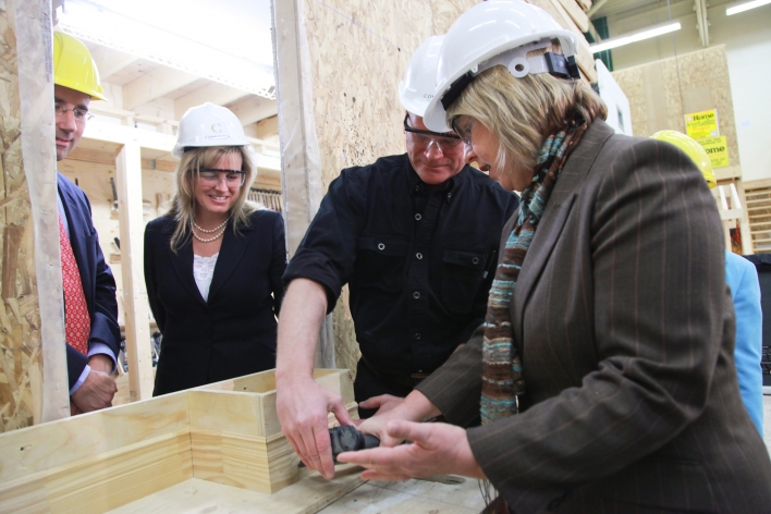 Mike Holmes supervises Deb Matthews, Minister Responsible for Women's Issues, use of a nail gun while John Milloy, Minister of Trainings, Colleges and Universities, and PA Leeana Pendergast look on.