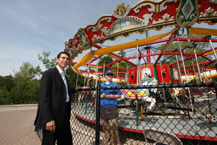 Minister Fonseca and Jasmine Pavoni talk about safety issues at the Storybook Gardens carousel.