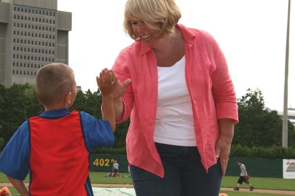 "Minister gives a ""high-five"" to Dyllan Patterson, age 7, at the Rookie League Baseball Training Camp."