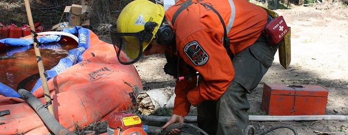 Un pompier du MRN installe une pompe et un réservoir d'eau portable.