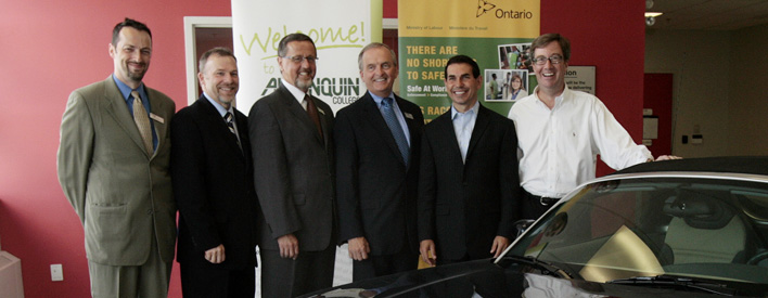 In front of Algonquin College's automotive shop. From Left: Bob Ledrew, Algonquin's Communications Director; Claude Brulé, Executive Dean of Algonquin's Faculty of Technology and Trades; Bob Letourneau, Vice-President of Algonquin College Administration; Robert C. Gillett, Algonquin College President; Peter Fonseca, Minister of Labour; Jim Watson, MPP for Ottawa West-Nepean.